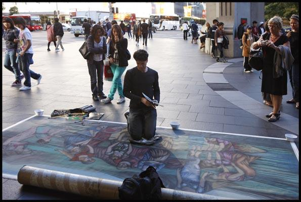 A street artist, busker, painting a large canvass on the pavement at the Queen Victoria Building